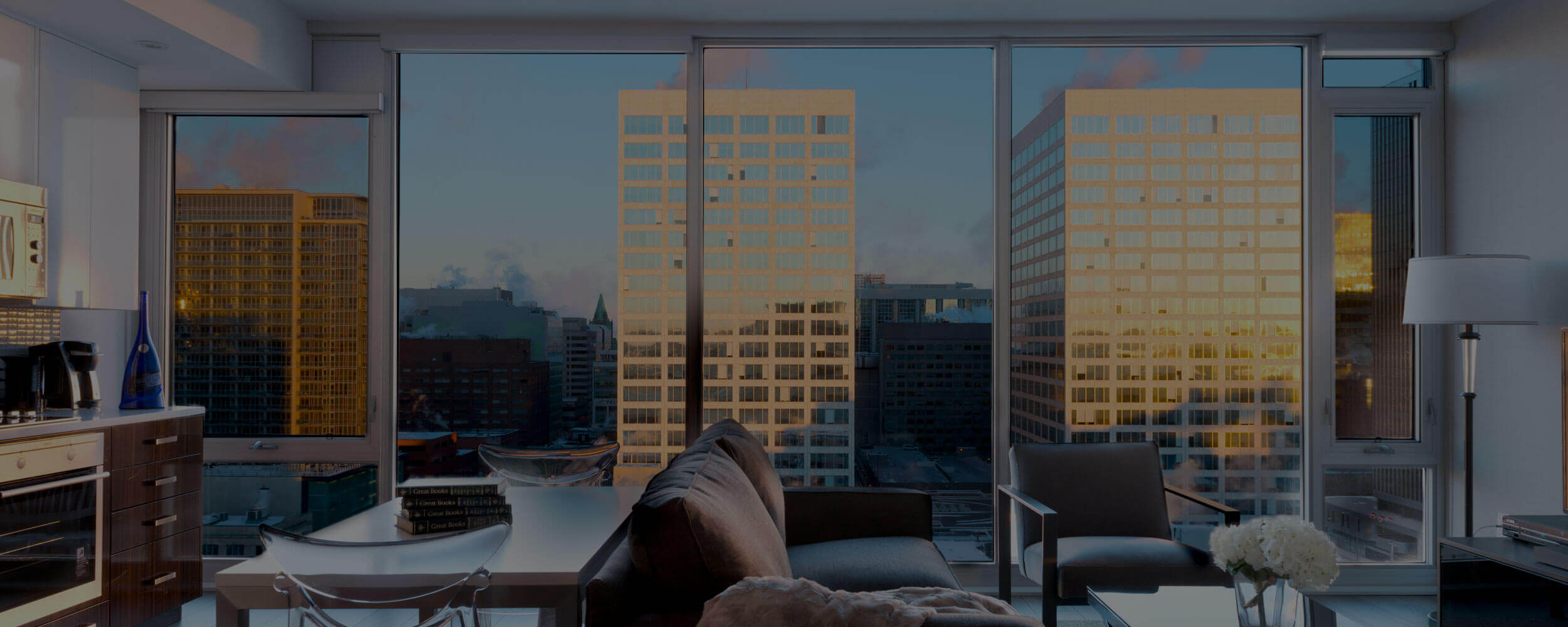 SoHo Lisgar Residences in Ottawa furnished bedroom suite with living and kitchen, overlooking downtown in evening