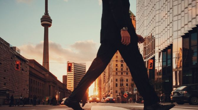 Shilouette of a man walking on the street with the CN tower in the background in Toronto