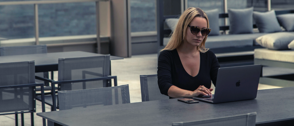 blonde woman wearing sunglasses sits on the terrace of the hotel working on her computer