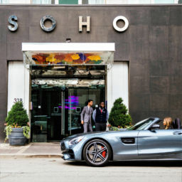 Blonde woman in a sports car pulls up to The SoHo Hotel's valet service