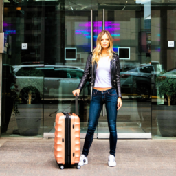 Blonde woman with pink luggage stands in front of The SoHo Hotel entrance