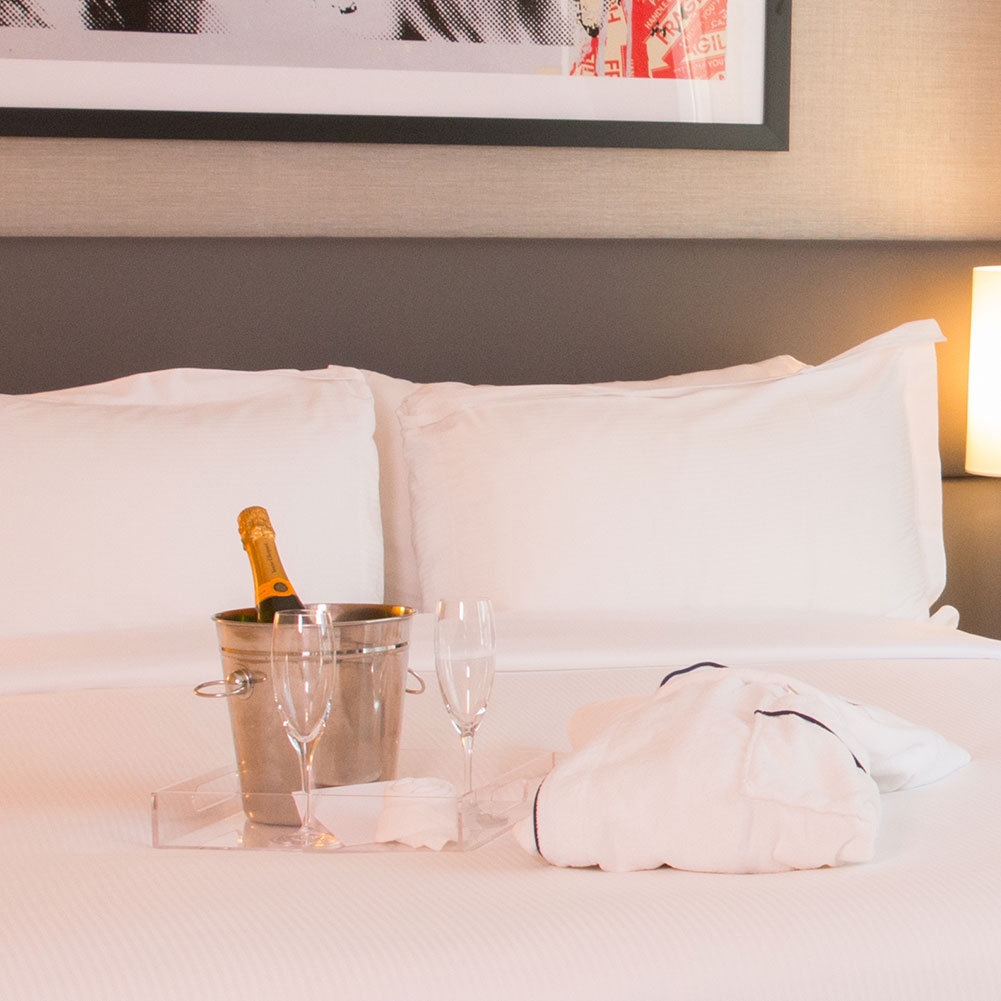 Bubbly and Robe on a bed at The SoHo Hotel